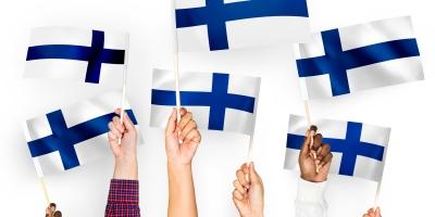 Kädet, jotka heiluttavat suomenlippua.