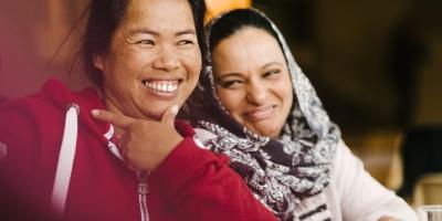 Kaksi naista hymyilevät.